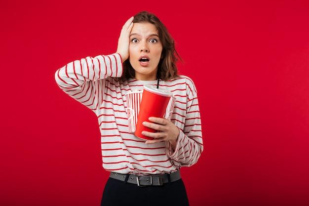 Portret zdziwiona kobieta trzyma popcorn