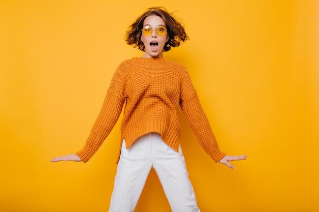 Portret zdziwiona młoda kobieta w białych spodniach, skoki przed żółtą ścianą