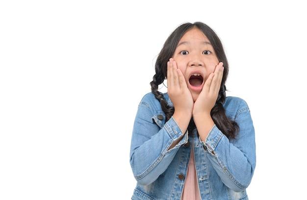 Portret zdziwiona śliczna mała azjatykcia dziewczyna dziecko pozycja odizolowywająca nad białym tłem. patrząc na kamerę i otwarte usta, koncepcja twarzy emocji