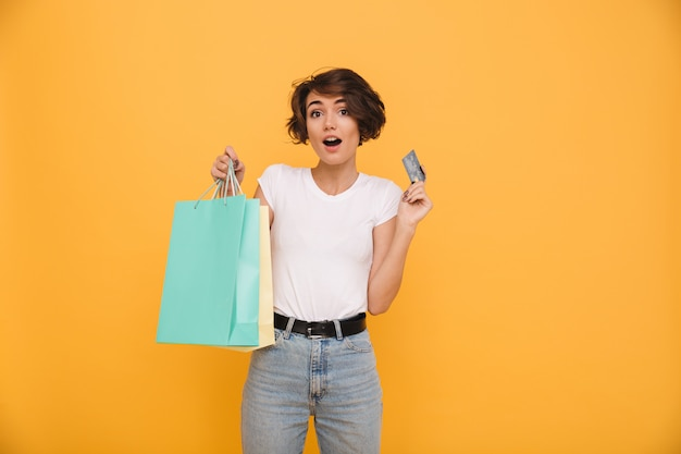 Portret zdziwiona szczęśliwa kobiety mienia torba na zakupy