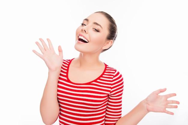 Portret zdziwiona szczęśliwa uśmiechnięta dziewczyna gestykuluje rękami