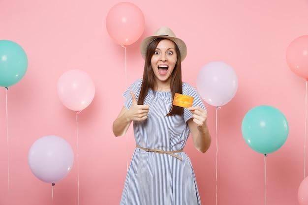 Portret zdziwiona zdziwiona kobieta w słomkowym letnim kapeluszu niebieska sukienka trzymając kartę kredytową pokazując kciuk na różowym tle z kolorowymi balonami. urodziny wakacje party ludzie szczere emocje.