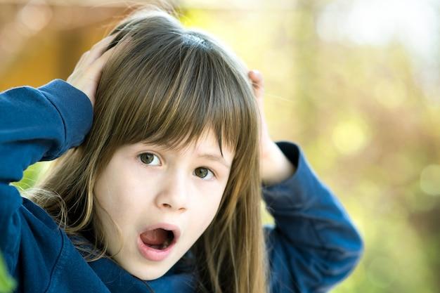 Portret zdziwione dziecko dziewczyny mienia ręki jej głowa outdoors w lecie. zszokowana dziewczynka w ciepły dzień na zewnątrz.