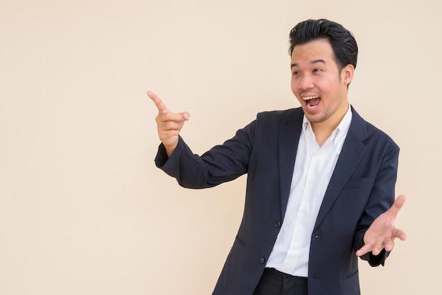 Portret zdziwionego azjatyckiego biznesmena noszącego garnitur na prostym tle
