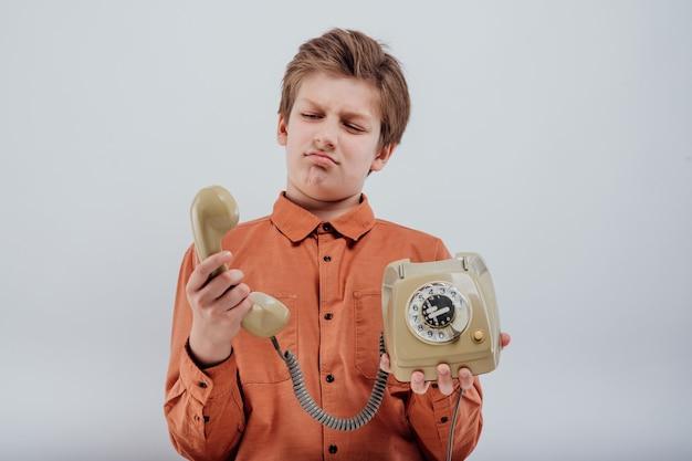 Portret zdziwionego chłopca ze starym telefonem na białym tle