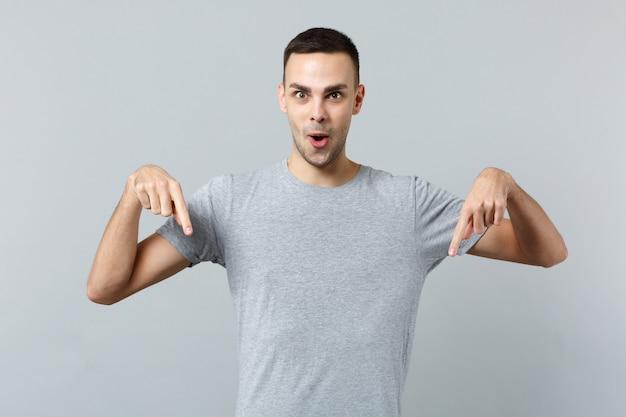 Portret zdziwionego, zszokowanego młodego mężczyzny w zwykłych ubraniach, stojącego, wskazującego palce wskazujące w dół