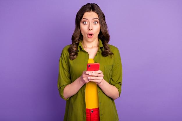 Portret zdziwionej dziewczyny używa telefonu komórkowego pod wrażeniem informacji z mediów społecznościowych, gapi się na osłupienie, nosi dobrze wyglądające ubrania odizolowane na fioletowym tle