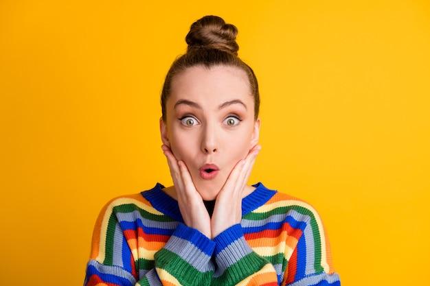 Portret zdziwionej dziewczyny wygląda niesamowicie okazja nowość dotknąć ręce twarz policzki kości policzkowe nosić sweter na białym tle nad jasnym kolorem tła
