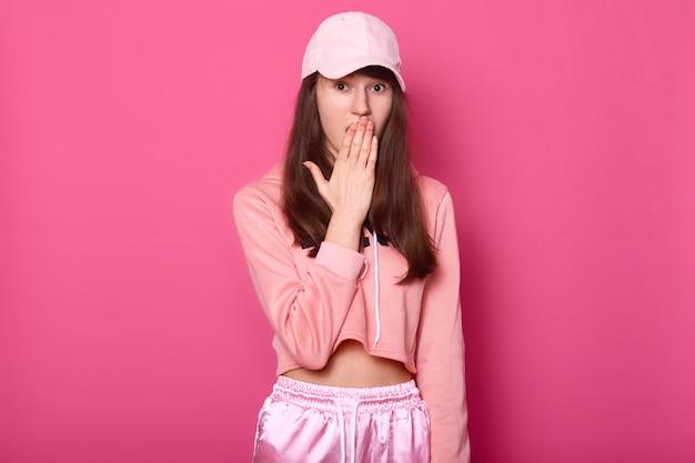 Portret zdziwionej europejskiej brunetki zakrywa dłonią otwarte usta, ubrany w stylowe różowe spodnie dresowe, bluzę z kapturem i czapkę, stoi przy różowej ścianie studia. koncepcja ludzi i emocji.