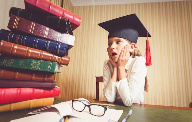 Portret zdziwionej inteligentnej dziewczyny w czapce ukończenia szkoły, patrzącej na duży stos książek