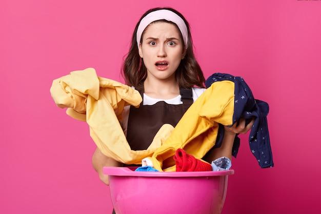 Portret zdziwionej kobiety z ogromną różową umywalką ze świeżymi ubraniami i artykułami domowymi