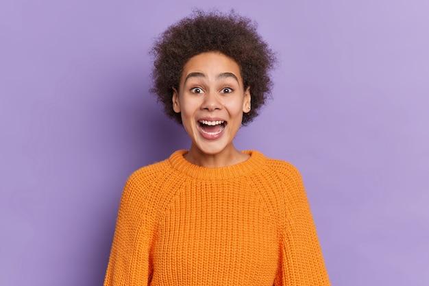 Portret zdziwionej kręconej kobiety z szeroko otwartymi ustami reaguje na niesamowitą niespodziankę, której wyrazem jest rozradowany, ubrany w pomarańczowy sweter z dzianiny.