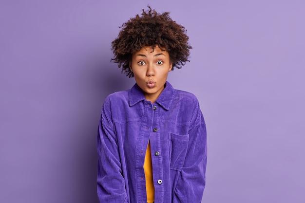 Portret zdziwionej, kręconej, młodej afroamerykanki, której usta są zaokrąglone, chce pocałować kogoś ubranego w stylowe ubranie