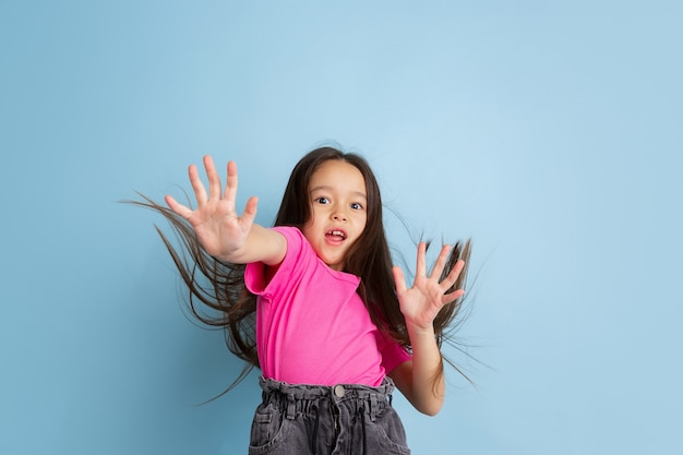 Portret zdziwionej małej dziewczynki w niebieskim studio