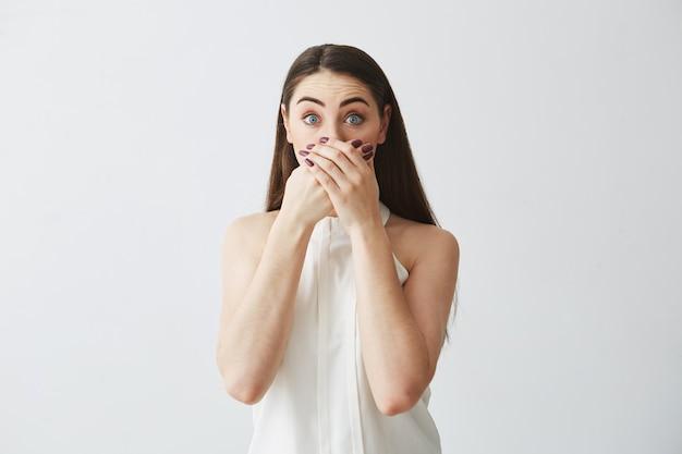 Portret zdziwionej młodej brunetki dziewczyny nakrywkowy usta z ręką.