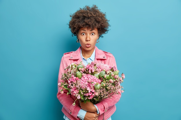 Portret zdziwionej młodej kobiety z kręconymi włosami obejmuje duży ładny bukiet kwiatów zszokowany, aby otrzymać gratulacje z okazji urodzin odizolowany na niebieskiej ścianie