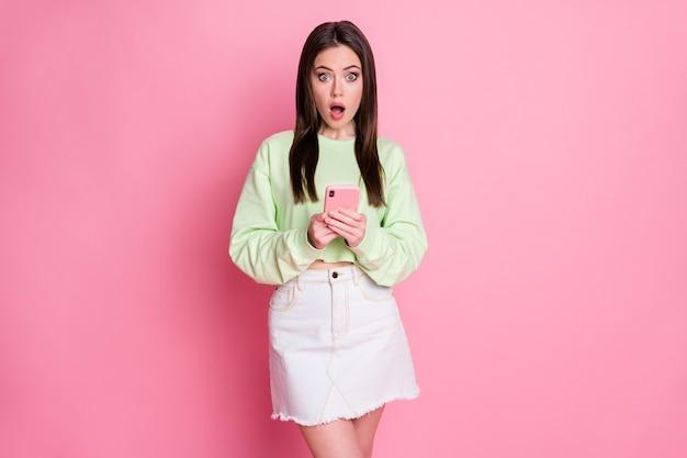 Portret zdziwionej młodszej dziewczyny używa telefonu komórkowego pod wrażeniem informacji w mediach społecznościowych nosi biały zielony sweter na białym tle pastelowy kolor