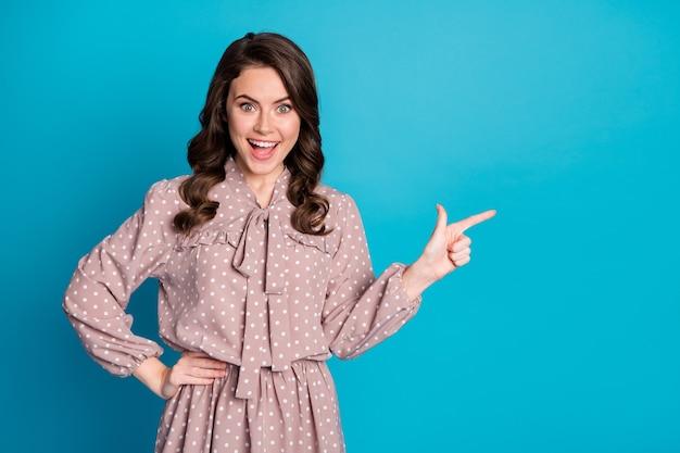 Portret zdziwionej pozytywnej dziewczyny punkt wskazujący palec copyspace prezentuje niesamowite reklamy promocyjne rabaty pod wrażeniem krzyk wow omg nosić dobry wygląd koszuli na białym tle niebieski kolor tła