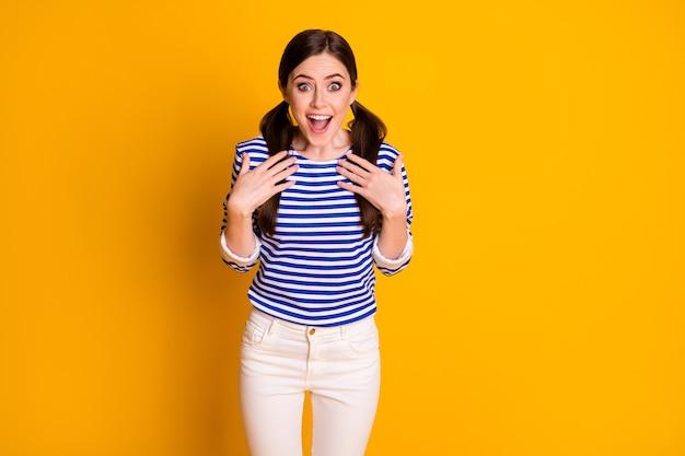Portret zdziwionej pozytywnej dziewczyny słyszy, jak wybiera, decyduje się na letnie wakacje pod wrażeniem punktu, w którym ręce noszą dobrze wyglądające ubrania odizolowane na jasnym kolorowym tle
