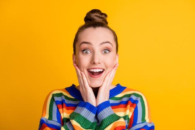 Portret zdziwionej pozytywnej dziewczyny wygląda cudownie nowość pod wrażeniem dotyku twarz ręce policzki kości policzkowe noszą sweter na białym tle nad połyskiem koloru tła