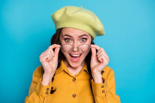 Portret zdziwionej pozytywnej dziewczyny wygląda na cudowną nowość pod wrażeniem krzyku dotyk specyfikacje noszą żółty strój nakrycia głowy izolowane na niebieskim tle