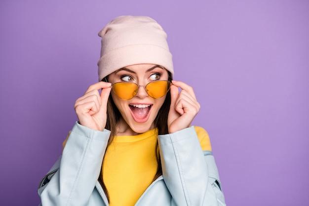 Portret zdziwionej pozytywnej szalonej młodej dziewczyny wygląda na copyspace zobacz niesamowitą nowość pod wrażeniem krzyku nosić casualowe ubrania w nowoczesnym stylu odizolowane na fioletowym tle