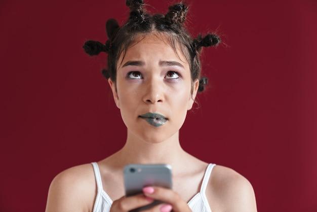 Portret zdziwionej punkowej dziewczyny z dziwaczną fryzurą i makijażem, patrzącą w górę na copyspace, trzymając smartfona izolowanego nad czerwoną ścianą