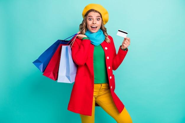 Portret zdziwionej szalonej dziewczyny pod wrażeniem sprzedaży w centrum handlowym kup wiele torebek zapłać kartą kredytową nosić czerwony zielony sweter niebieskie żółte spodnie spodnie na białym tle nad turkusowym kolorem tła