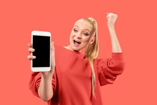 Portret zdziwionej, uśmiechniętej, szczęśliwej, zdumionej dziewczyny pokazującej pusty ekran telefonu komórkowego na białym tle nad koralowym tłem.