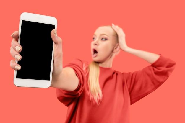 Portret zdziwionej, uśmiechniętej, szczęśliwej, zdumionej dziewczyny pokazującej pusty ekran telefonu komórkowego na białym tle nad ścianą koralowca