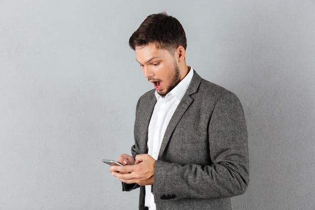 Portret zdziwiony biznesmen patrzeje telefon komórkowego