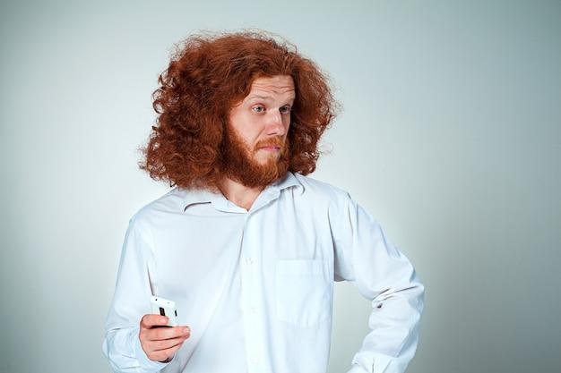 Portret zdziwiony mężczyzna rozmawia przez telefon szara ściana