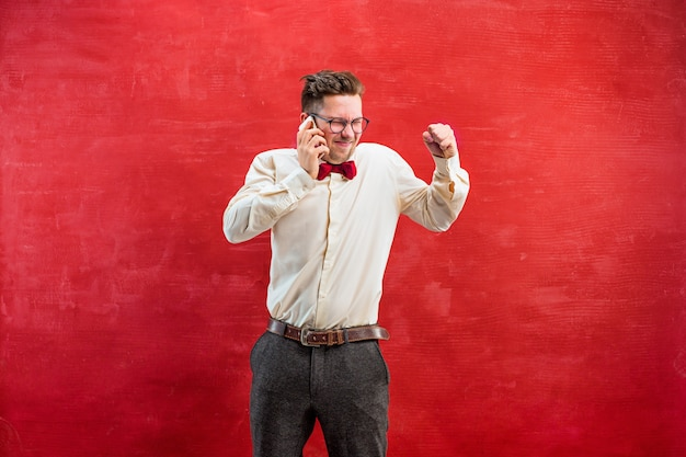 Portret zdziwiony mężczyzna w okularach rozmawia przez telefon w czerwonym studio