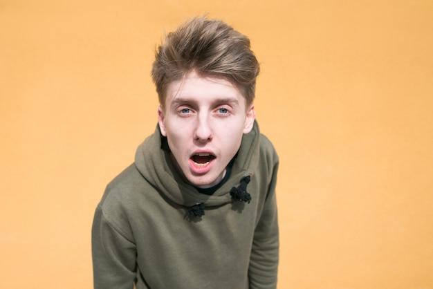 Portret zdziwiony młody człowiek na pomarańczowej ścianie.