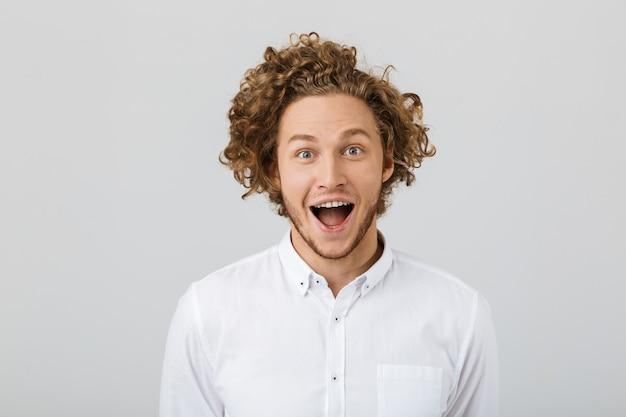 Portret zdziwiony młody człowiek z kręconymi włosami