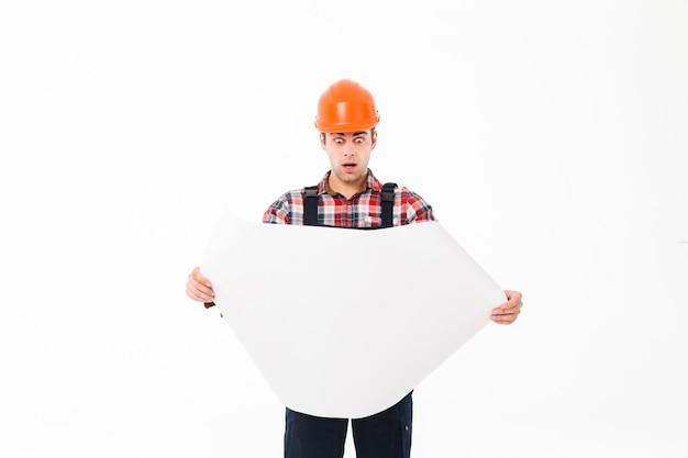 Portret zdziwiony młody męski budowniczy egzamininuje papierowego szkic