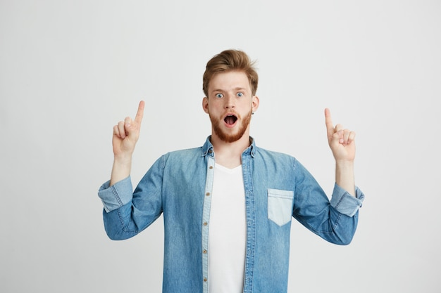 Portret zdziwiony młody przystojny mężczyzna wskazuje palec up z rozpieczętowanym usta.