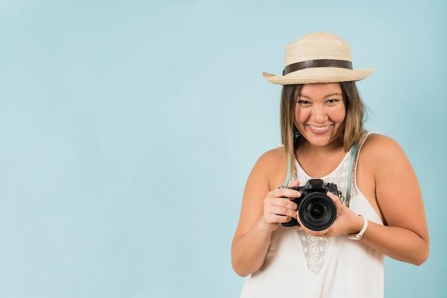 Portret żeński fotograf pozuje z jej fachową kamerą przeciw błękitnemu tłu