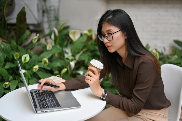 Portret żeński freelancer trzymając papierowy kubek i ręcznie wpisując na laptopie podczas pracy na świeżym powietrzu w ogrodzie