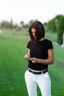 Portret żeński golfisty writing na wynik karcie podczas gdy stojący przy polem golfowym. kobieta pisze w słoneczny dzień na zewnątrz