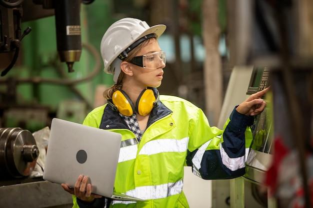 Portret żeński inżynier obsługi maszyny przez laptop w fabryce