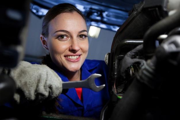Portret żeński mechanik bada silnika samochodu