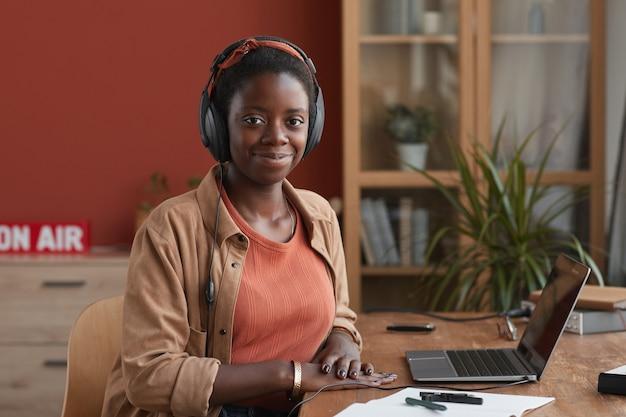 Portret żeński muzyk african-american uśmiecha się do kamery i za pomocą laptopa podczas tworzenia muzyki w domu, kopia przestrzeń