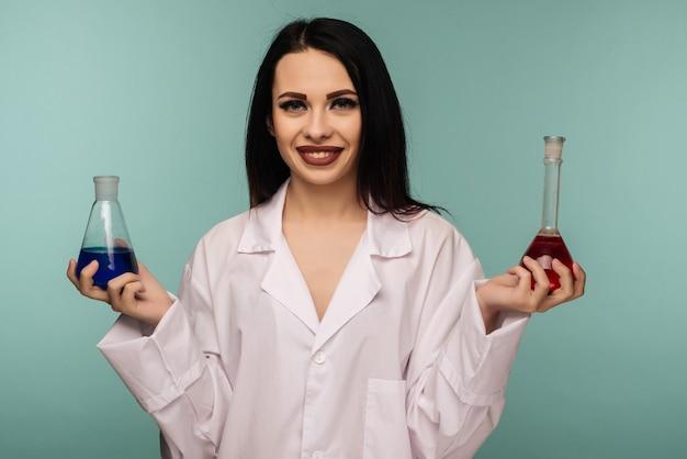 Portret żeński naukowiec bada kolby z różnymi substancjami chemicznymi w laboratorium medycznym - obraz