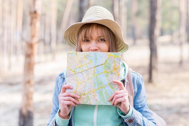 Portret żeński podróżnik trzyma mapę przed jej usta patrzeje kamerę