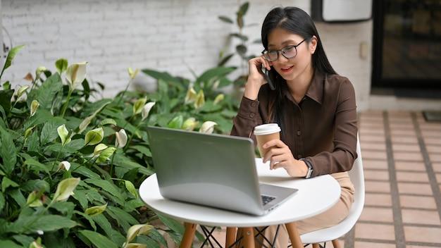 Portret żeński pracownik biurowy relaks i dzwoniąc na telefon podczas pracy na świeżym powietrzu w ogrodzie