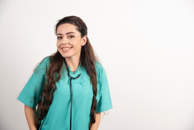 Portret żeński pracownik opieki zdrowotnej pozowanie na białej ścianie.