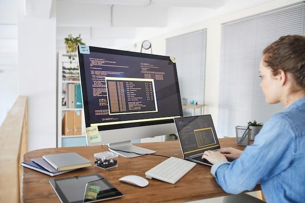 Portret żeński programista it wpisując na klawiaturze z czarnym i pomarańczowym kodem programowania na ekranie komputera i laptopa we współczesnym wnętrzu biurowym, miejsce na kopię