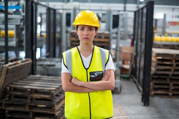 Portret żeńskiego pracownika pozycja z rękami krzyżować