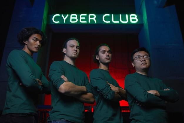 Portret zespołu graczy stojących z rękami skrzyżowanymi i patrząc na kamery grają w klubie komputerowym